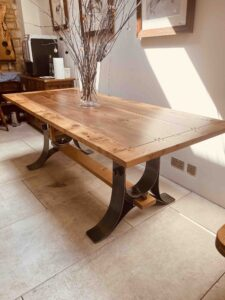 new - 7. Burr oak and walnut table on 'swept knot' forged steel base, with floor level stretcher, 84_ x 36_ (2103 x 915mm), satin wax oil finish, seats 6_8, £3,995